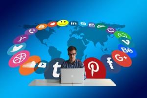 Mann am Computer mit Logos verschiedener Social-Media-Plattformen